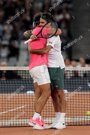 Stock Image of Roger Federer, right, and Rafael Nadal embrace after the final point of their exhibition tennis match held at the Cape Town Stadium in Cape Town, South Africa