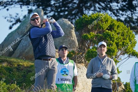 Peyton Manning, left, follows his shot from the 11th tee of the Monterey Peninsula Country Club Shore Course as his brother, Eli Manning, looks on during the second round of the AT&T Pebble Beach National Pro-Am golf tournament, in Pebble Beach, Calif