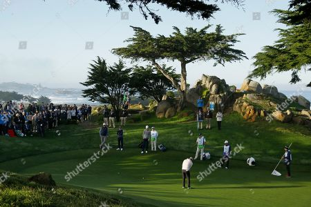 Kevin Chappell, Peyton Manning, Eli Manning. Kevin Chappell putts on the 10th green of the Monterey Peninsula Country Club Shore Course during the second round of the AT&T Pebble Beach National Pro-Am golf tournament, in Pebble Beach, Calif. Looking on from left are Peyton Manning, Luke Donald and Eli Manning