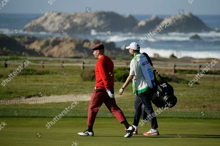 Macklemore walks with his caddie along the 12th fairway of the Monterey Peninsula Country Club Shore Course during the second round of the AT&T Pebble Beach National Pro-Am golf tournament, in Pebble Beach, Calif