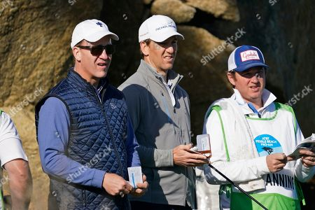 Peyton Manning, left, and his brother, Eli Manning, wait to hit from the 16th tee of the Monterey Peninsula Country Club Shore Course during the second round of the AT&T Pebble Beach National Pro-Am golf tournament, in Pebble Beach, Calif