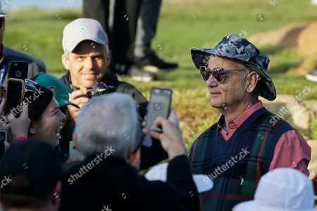 Bill Murray models a fan's sunglasses on the 10th green of the Monterey Peninsula Country Club Shore Course during the second round of the AT&T Pebble Beach National Pro-Am golf tournament, in Pebble Beach, Calif