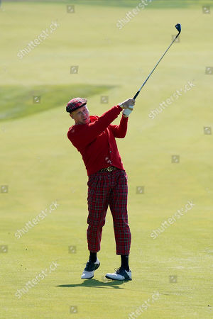 Singer Macklemore hits a ball from the sixth fairway of the Monterey Peninsula County Club Shore Course during the second round of the AT&T Pebble Beach National Pro-Am golf tournament, in Pebble Beach, Calif