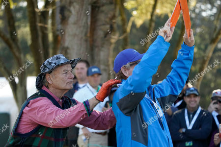 Bill Murray massages a volunteers shoulders on the fifth tee of the Monterey Peninsula County Club Shore Course during the second round of the AT&T Pebble Beach National Pro-Am golf tournament, in Pebble Beach, Calif