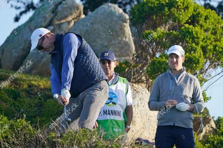 Peyton Manning hits from the 11th tee of the Monterey Peninsula Country Club Shore Course as his brother Eli Manning looks on during the second round of the AT&T Pebble Beach National Pro-Am golf tournament, in Pebble Beach, Calif