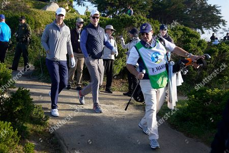 Eli Manning, left, and brother Peyton Manning walk to the green on the 11th hole of the Monterey Peninsula County Club Shore Course during the second round of the AT&T Pebble Beach National Pro-Am golf tournament, in Pebble Beach, Calif
