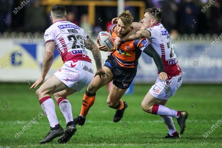 CastlefordÕs Danny Richardson is tackled by WiganÕs Harry Smith.