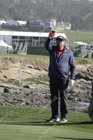 Stock Image of Toby Keith plays approach shot to the 18th and acknowledges the crowd