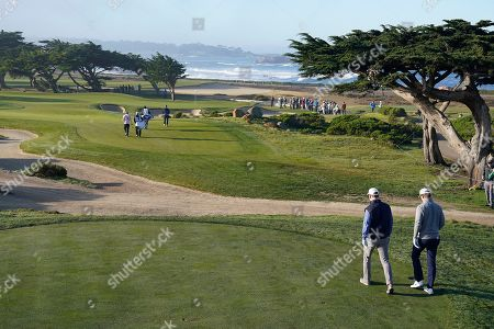 Eli Manning, right, and brother Peyton Manning walk to the green on the 11th hole of the Monterey Peninsula County Club Shore Course during the second round of the AT&T Pebble Beach National Pro-Am golf tournament, in Pebble Beach, Calif