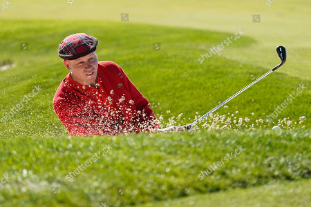 Rapper Macklemore hits out of a bunker on the sixth green of the Monterey Peninsula County Club Shore Course during the second round of the AT&T Pebble Beach National Pro-Am golf tournament, in Pebble Beach, Calif
