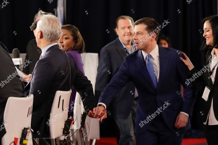 Democratic presidential candidate former South Bend Mayor Pete Buttigieg, right, reaches to greet former Chicago Mayor Rahm Emanuel, left, in raw media spinroom after participating in the Democratic presidential primary debate hosted by ABC News, Apple News, and WMUR-TV at Saint Anselm College in Manchester, N.H