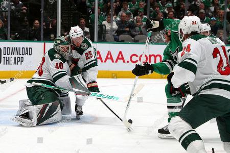 Minnesota Wild goaltender Devan Dubnyk (40) and defenseman Jonas Brodin (25) defend as Dallas Stars center Joe Pavelski (16) shoots in the first period during an NHL hockey game, in Dallas