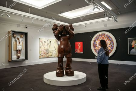 Stock Picture of A staff member views Kaw's wooden sculpture 'Afromosia wood' (Est £700,000 - £900,000) at the preview of Sotheby's Contemporary Art.
