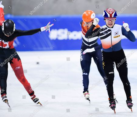 Canada's Courtney Lee Sarault, left, pushes her skate across the finish line to take a second place as Korea's Kim Ji-yoo celebrates winning the women's 1000 meters final ahead of third placed Netherlands' Suzanne Schulting, rear, during the World Cup short track speed skating championship in Dresden, eastern Germany