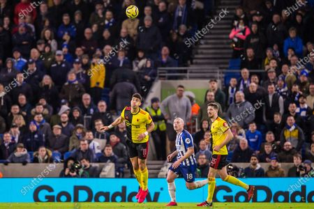 Adam Masina (Watford) heads the ball as Aaron Mooy (Brighton) & Craig Cathcart (Watford) look on during the Premier League match between Brighton and Hove Albion and Watford at the American Express Community Stadium, Brighton and Hove