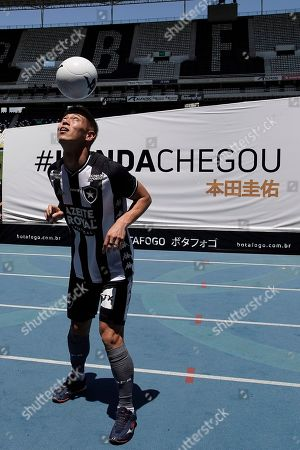 Japan's Keisuke Honda controls the ball during his presentation as the new soccer player of Botafogo soccer club at the Nilton Santos stadium in Rio de Janeiro, Brazil, . Honda, considered one of Japan's most successful players who played in the last three World Cups, has signed on to play for Botafogo