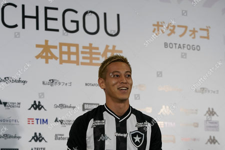 Japan's Keisuke Honda poses for the pictures wearing his Botafogo jersey during his official presentation as the newest member of the Brazilian soccer club, in Rio de Janeiro, Brazil, . Honda, considered one of Japan's most successful players who played in the last three World Cups, has signed on to play for Botafogo