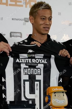 Japan's Keisuke Honda poses for the pictures holding his Botafogo jersey during his official presentation as the newest member of the Brazilian soccer club, in Rio de Janeiro, Brazil, . Honda, considered one of Japan's most successful players who played in the last three World Cups, has signed on to play for Botafogo
