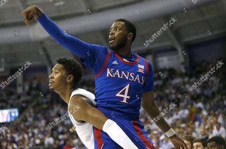Kansas guard Isaiah Moss (4) scores on a 3-point shot as TCU forward Diante Smith (10) looks on during the first half of an NCAA college basketball game, in Fort Worth, Texas