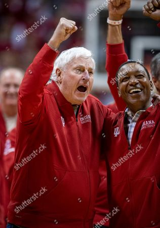 """Former Indiana basketball head coach Bobby Knight, left, yells """"play defense!"""" for the fans during his first appearance at Indiana University since his dismissal in September of 2000. Knight, along with former player Isiah Thomas, right, are on the court during a ceremony with the Indiana players of the 1980 Big Ten championship team the halftime of an NCAA college basketball game, in Bloomington, Ind"""