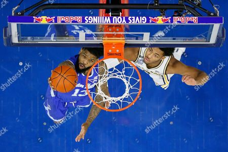 Stock Image of Justin Moore, Myles Powell. Seton Hall's Myles Powell, left, goes up for a shot past Villanova's Justin Moore during the first half of an NCAA college basketball game, in Philadelphia