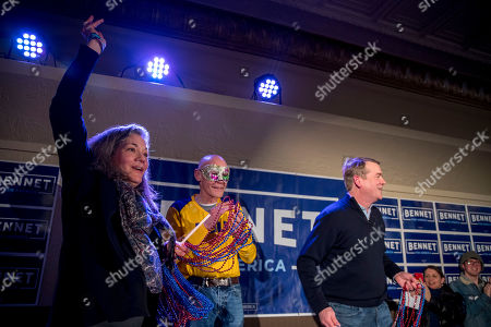 Susan Daggett, James Carville, Michael Bennet. James Carville, a political commentator known for leading former President Bill Clinton's 1992 presidential campaign, center, wears a mardi gras mask Democratic presidential candidate Sen. Michael Bennet, D-Colo., right, and his wife Susan Daggett, left, throw beads into the audience during a campaign stop at the Spotlight Room at the Palace, in Manchester, N.H