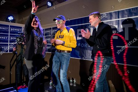 Susan Daggett, James Carville, Michael Bennet. James Carville, a political commentator known for leading former President Bill Clinton's 1992 presidential campaign, center, wears a mardi gras mask as Democratic presidential candidate Sen. Michael Bennet, D-Colo., right, and his wife Susan Daggett, left, throw beads into the audience during a campaign stop at the Spotlight Room at the Palace, in Manchester, N.H
