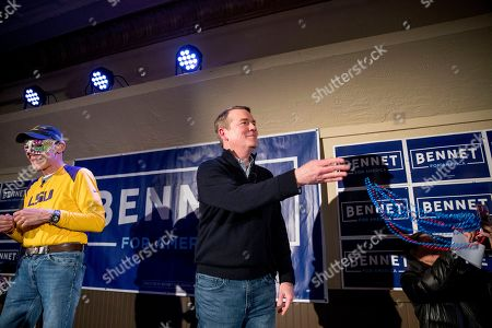 Stock Photo of James Carville, Michael Bennet. James Carville, a political commentator known for leading former President Bill Clinton's 1992 presidential campaign, left, wears a mardi gras mask as Democratic presidential candidate Sen. Michael Bennet, D-Colo., throws beads into the audience during a campaign stop at the Spotlight Room at the Palace, in Manchester, N.H