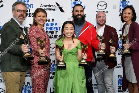 """Stock Photo of Peter Saraf, Daniele Melia, Lulu Wang, Andrew Miano, Eddie Rubin, Anita Gou. Peter Saraf, from left, Daniele Melia, Lulu Wang, Andrew Miano, Eddie Rubin, Anita Gou pose in the press room with the award for best feature for """"The Farewell"""" at the 35th Film Independent Spirit Awards, in Santa Monica, Calif. Lulu Wang, center, also poses with the award for best supporting female for """"The Farewell,"""" which she accepted on behalf of Zhao Shuzhen"""