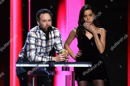 Jon Glaser, Aubrey Plaza. Jon Glaser, left, speaks while eating a sandwich onstage while Aubrey Plaza looks on at the 35th Film Independent Spirit Awards, in Santa Monica, Calif