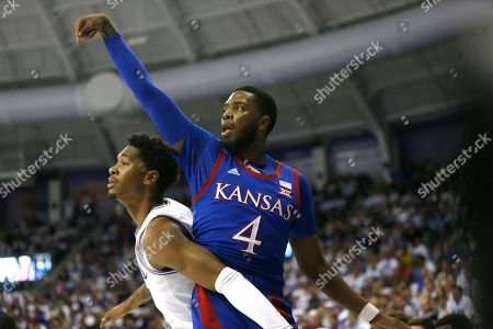 Isaiah Moss; Diante Smith. Kansas guard Isaiah Moss (4) scores on a three point shot as TCU forward Diante Smith (10) looks on during the first half of an NCAA college basketball game, in Fort Worth, Texas