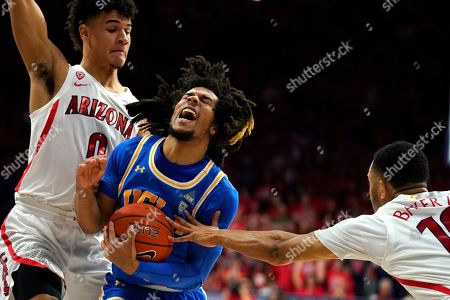 Stock Photo of UCLA guard Tyger Campbell (10) drives between Arizona's Josh Green (0) and Jemarl Baker Jr. during the first half of an NCAA college basketball game, in Tucson, Ariz