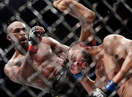 Jon Jones, left, delivers a kick to Dominick Reyes, right, during a light heavyweight mixed martial arts bout at UFC 247, in Houston
