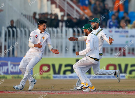 Pakistan pacer Naseem Shah celebrates with teammates after taking the wicket of Bangladesh batsman Mahmudullah during the third day of their 1st test cricket match at Rawalpindi cricket stadium in Rawalpindi, Pakistan