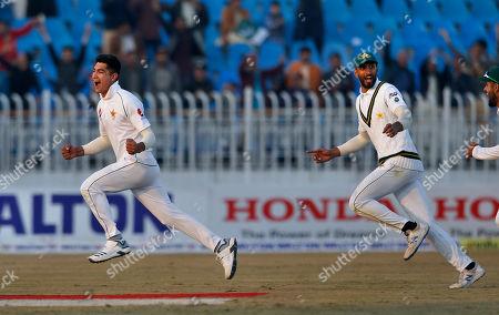 Pakistan pacer Naseem Shah, left celebrates with teammates after taking the wicket of Bangladesh batsman Mahmudullah during the third day of their 1st test cricket match at Rawalpindi cricket stadium in Rawalpindi, Pakistan
