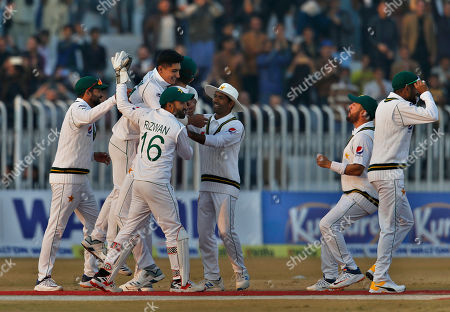 Pakistan pacer Naseem Shah, center without cap, celebrates with teammates after taking the wicket of Bangladesh batsman Mahmudullah during the third day of their 1st test cricket match at Rawalpindi cricket stadium in Rawalpindi, Pakistan
