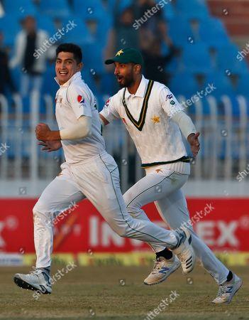 Pakistan pacer Naseem Shah, left, celebrates with teammate Shan Masood after taking the wicket of Bangladesh batsman Mahmudullah during the third day of their 1st test cricket match at Rawalpindi cricket stadium in Rawalpindi, Pakistan