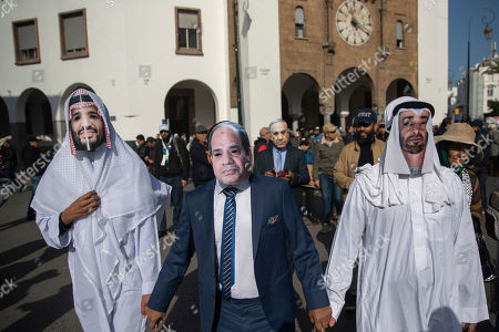 People wear masks depicting foreground right, Dubai Crown Prince Sheikh Mohammed Bin Zayed, Egypt's President Abdel Fattah al-Sisi, and Saudi Crown Prince Mohammad bin Salman bin Abdulaziz Al Saud, and Israeli Prime Minister Benjamin Netanyahu, background, during a demonstration in Rabat, Morocco,. Thousands of Moroccans took part in a march rejecting Trump's Middle East peace plan and in support of Palestinians