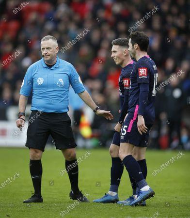Referee Jon Moss talks to Harry Wilson and Adam Smith of Bournemouth