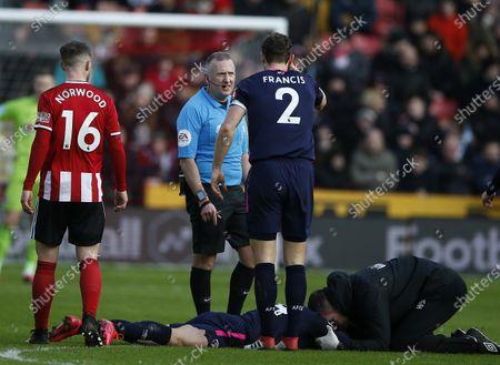 Referee Jon Moss talks to Simon Francis of Bournemouth