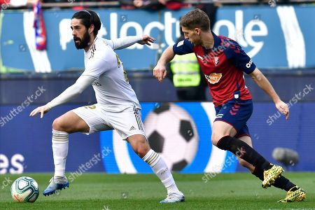 Real Madrid's Isco, left, vies for the ball with Osasuna's Roberto Torres during the Spanish La Liga soccer match between Osasuna and Real Madrid at El Sadar stadium in Pamplona, northern Spain