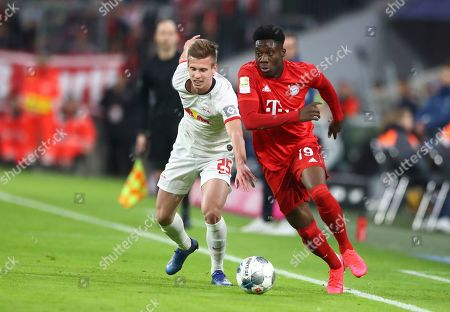 Leipzig's Daniel Carvajal, left, and Bayern's Alphonso Davies challenge for the ball during the German Bundesliga soccer match between Bayern Munich and RB Leipzig at the Allianz Arena in Munich, Germany