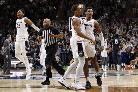 Stock Picture of Connecticut's Josh Carlton, left, Brendan Adams, center, and Christian Vital, right, react after they defeated Cincinnati as official Jeff Anderson runs off the court at the end of an NCAA college basketball game, in Storrs, Conn