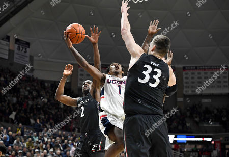 Connecticut's Christian Vital, center, shoots between Cincinnati's Keith Williams, left, and Chris Vogt, right, in the second half of an NCAA college basketball game, in Storrs, Conn