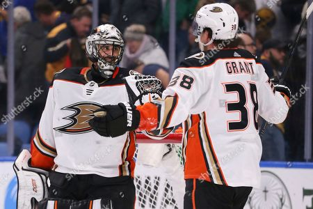 Anaheim Ducks goalie Ryan Miller (30) and forward Derek Grant (38) celebrate a 3-2 victory over the Buffalo Sabres following the third period of an NHL hockey game, in Buffalo, N.Y