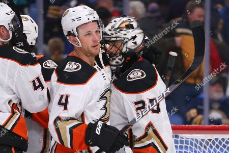Anaheim Ducks defenseman Cam Fowler (4) and goalie Ryan Miller (30) celebrate a 3-2 victory over the Buffalo Sabres following the third period of an NHL hockey game, in Buffalo, N.Y