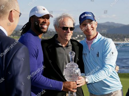 Larry Fitzgerald, Kevin Streelman, Clint Eastwood. Larry Fitzgerald, left, and Kevin Streelman, right, pose with their trophy and Clint Eastwood, center, at the Pebble Beach Golf Links after winning the team title of the AT&T Pebble Beach National Pro-Am golf tournament, in Pebble Beach, Calif