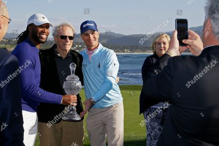Larry Fitzgerald, left, and Kevin Streelman pose with their trophy and Clint Eastwood, center, on the 18th green of the Pebble Beach Golf Links after winning the team title of the AT&T Pebble Beach National Pro-Am golf tournament, in Pebble Beach, Calif