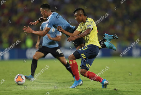 Uruguay's Jose Rodriguez, center, is taken down by Colombia's Luis Sandoval during a South America Olympic qualifying U23 soccer match at the Alfonso Lopez stadium in Bucaramanga, Colombia