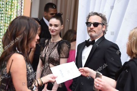 Rooney Mara, Joaquin Phoenix. Rooney Mara, left, and Joaquin Phoenix arrive at the Oscars, at the Dolby Theatre in Los Angeles